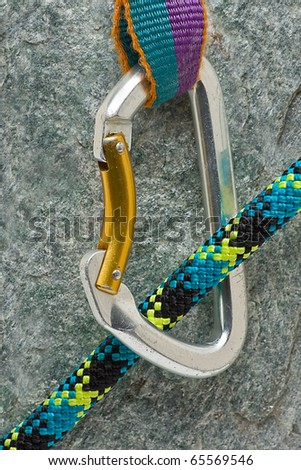 Climbing clip with rope over rock background - stock photo