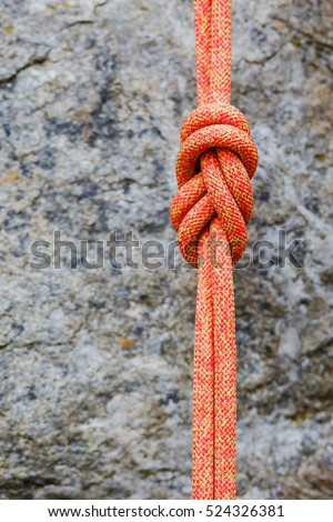 Climbing eight rope knot on rocky background
