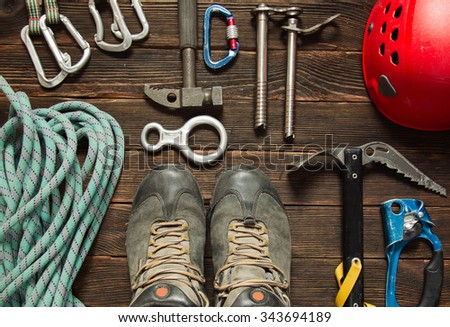 climbing equipment: blue rope, red helmet, hammer, trekking shoes and other set  on dark wooden background, top view - stock photo