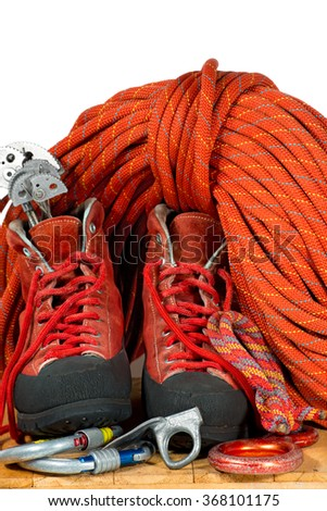 Climbing Equipment on White Background / Rock climbing equipment with mountaineering boots, climbing cams, descender, carabiners, piton, and a red rope. Isolated on white background