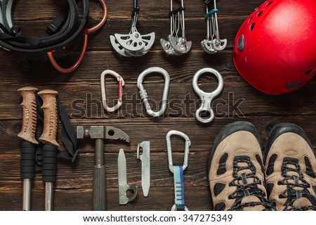 climbing equipment: red helmet, hammer, carabiner, trekking shoes and other set  on dark wooden background, top view - stock photo