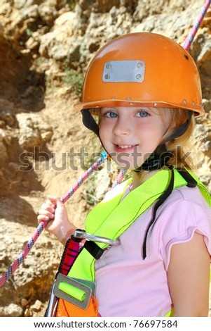 climbing little girl portrait helmet rope safety harness smiling - stock photo