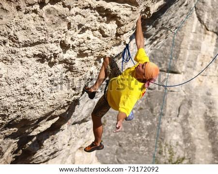 Climbing man playing of sport on high rocks - stock photo