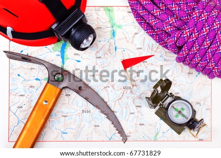 climbing map with compass and mountaineering equipment - stock photo