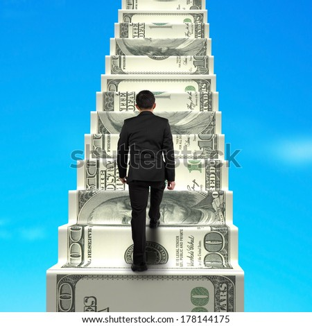 Climbing on money stairs with blue sky - stock photo