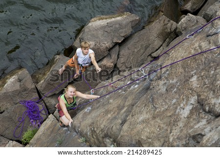 Climbing partners make ascent on to the rock wall Two climbers - male and female - climb rocky wall. They climb over the river rocky beach with impressive stones - stock photo