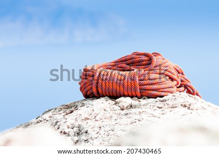 Climbing Rope coiled up and placed on the rock  - stock photo