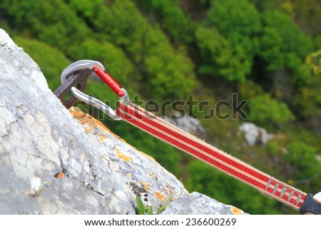 Climbing sling attached with a carabiner to rusty piton  - stock photo