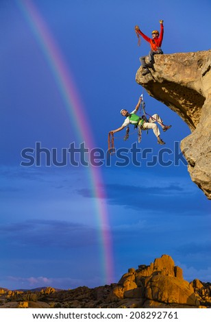 Climbing team celebrate a clearing storm on the edge of a cliff.