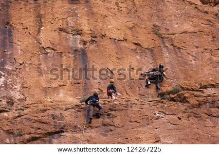 Climbing team exploring a calcite wall in Morocco - stock photo