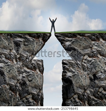 Climbing to success concept on a mountain and reaching the peak and summit as a businessman with arms in the air standing on top of two cliff sides shaped as an arrow symbol. - stock photo