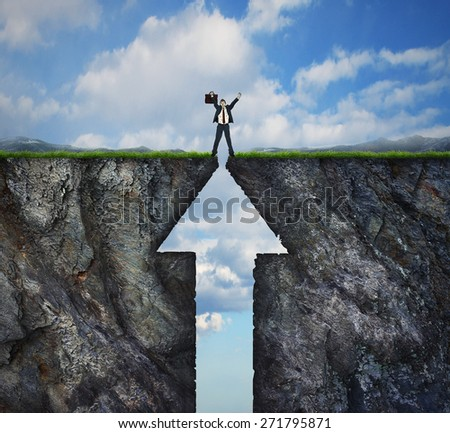 Climbing to success concept on mountain and reaching the peak summit. Businessman with arms in the air standing on top of two cliff sides shaped as an arrow symbol. - stock photo