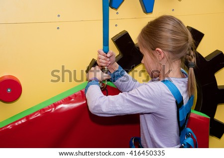 Climbing wall for children. The parkour Park, climbing wall and trampolines. The little girl on the climbing wall. Vacation, holiday. - stock photo