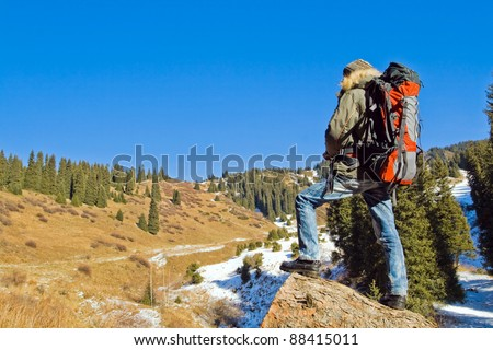 Climbing young adult at the top of summit with aerial view of blue sky and mountain