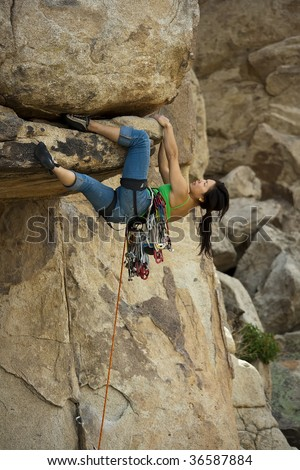 Clinging to an overhang a female climber is focused on her next move as she battles her way up a steep crack in Joshua Tree National Park, California.