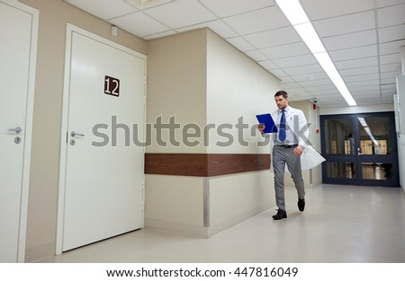 clinic, people, health care and medicine concept - doctor with clipboard walking along hospital corridor - stock photo