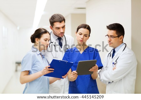 clinic, people, healthcare and medicine concept - group of medics or doctors with clipboards at hospital corridor - stock photo