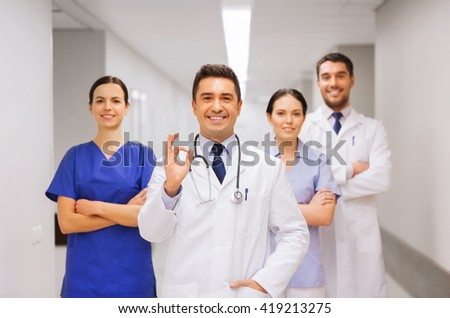 clinic, profession, people, health care and medicine concept - group of happy medics or doctors at hospital corridor showing ok hand sign - stock photo