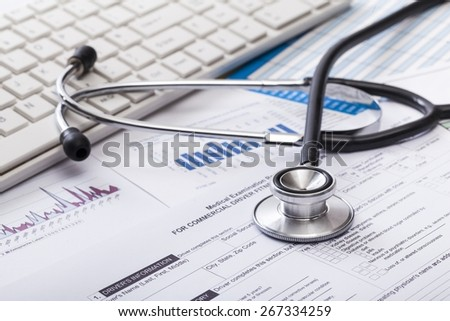 Clinic. Stethoscope with financial on the desk. - stock photo