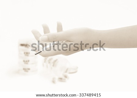clinical thermometer in hand with blur seven day pill box and capsule background