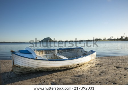 Clinker dinghy with classic style on the sand beach with the landmark Mount Maunganui across harbor on the horizon.. - stock photo