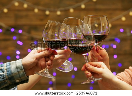Clinking glasses of red wine in hands on bright lights background - stock photo