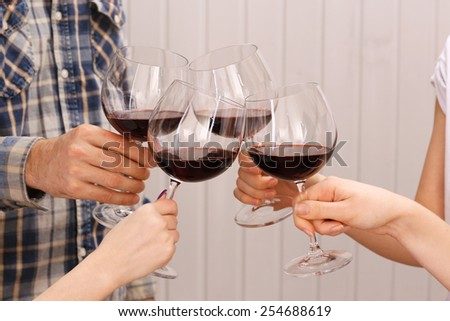 Clinking glasses of red wine in hands on color wooden planks background - stock photo
