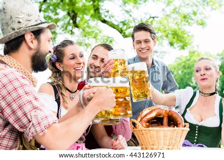 Clinking glasses with beer in Bavarian pub - stock photo