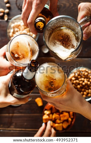 Clinking glasses with beer over wooden table, close-up on three beer glasses and two bottles