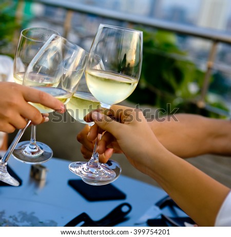 Clinking glasses with white wine - stock photo
