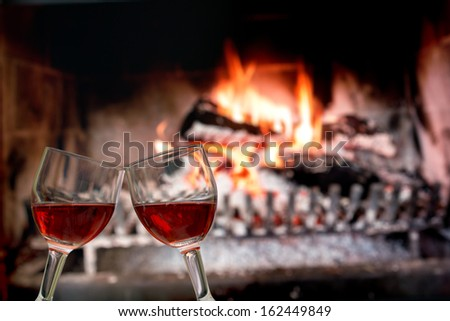 Clinking in front of fireplace. - stock photo