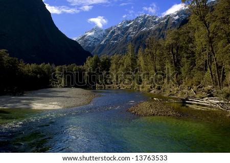 Clinton River along the Milford Track, Fiordland, New Zealand, with blue sky and amazing blue-green water - stock photo