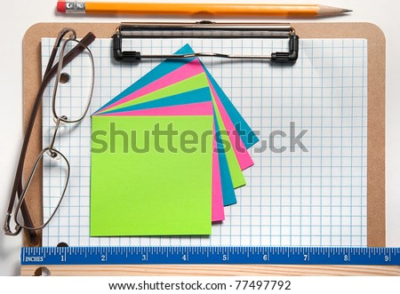 Clip board with grid paper, notes, pencil, ruler, and glasses with white background - stock photo