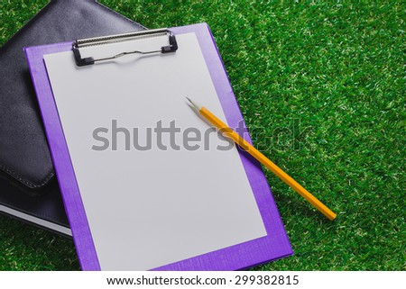 Clipboard, notepad on grass. Office outdoors
