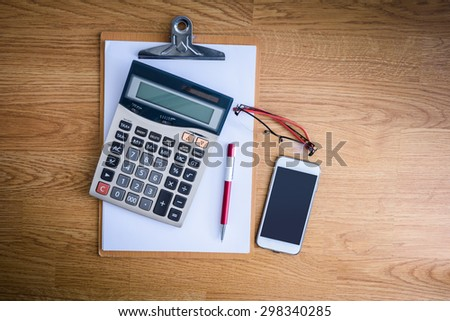 clipboard with a pen and  calculator, eyeglasses on office table - stock photo