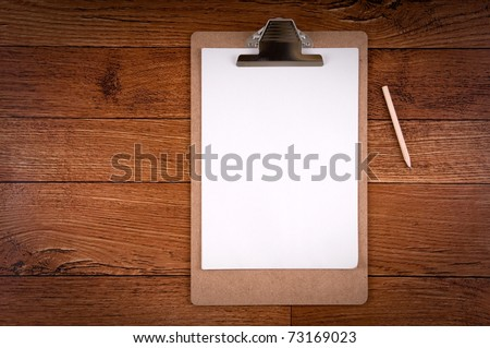 Clipboard with a sheet of paper and pencil on wood - a series of CONSTRUCTION IMAGES. - stock photo