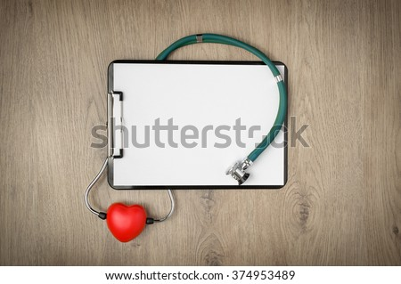 Clipboard with blank white paper, stethoscope and heart shape on wooden background - stock photo