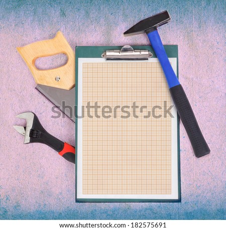 Clipboard with graph paper and tools over rough background - stock photo