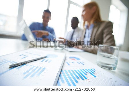 Clipboards and pen at workplace and business partners networking on background