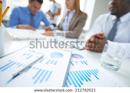 Clipboards, glass of water and pen at workplace with business partners on background