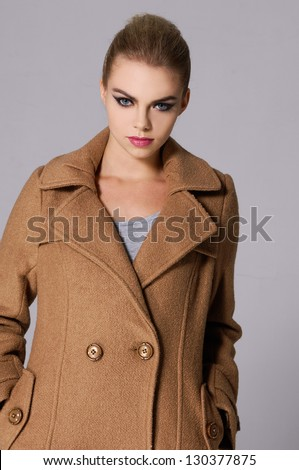 cloaeup portrait of a beautiful woman wearing coat - stock photo