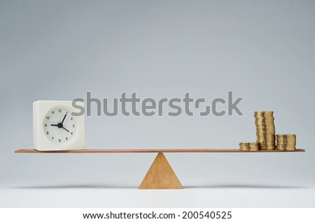Clock and money coins stack balancing on a seesaw - stock photo