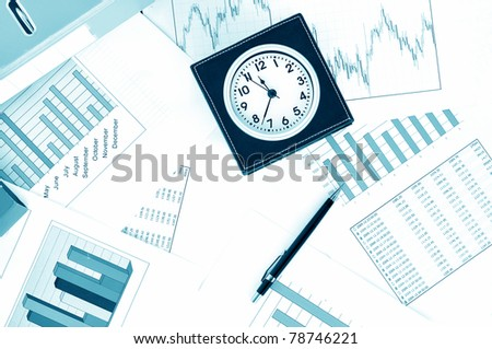 Clock and pen on a market report