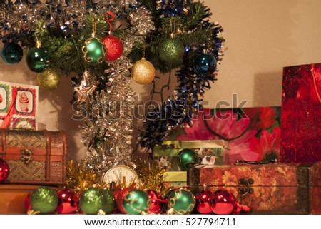 Clock and presents in front of Christmas tree with beautiful ornaments.