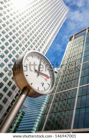 Clock and Skyscrapers at Canary Wharf, financial district in London. England
