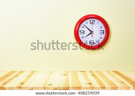 Clock and wood table with concrete wall background. - stock photo