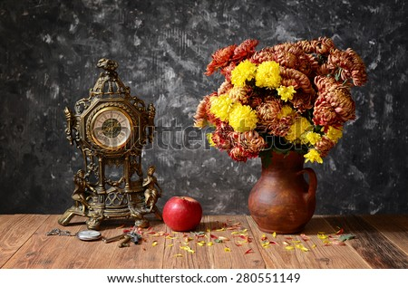 Clock, apples and flowers in a ceramic vase on the table - stock photo