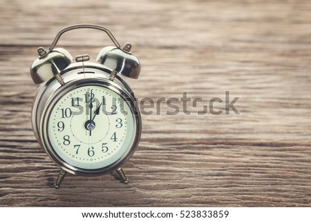 Clock at 1 pm. O'clock in the afternoon with vintage style alarm clock on a wooden table.
