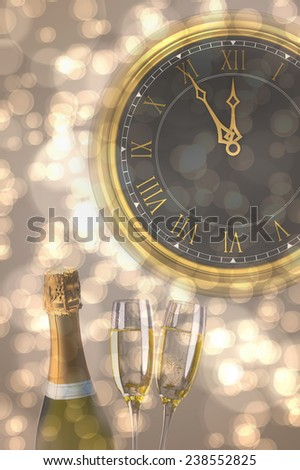 Clock counting down to midnight against sparkling wine
