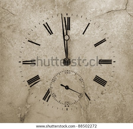 Clock face on a cracked stone. One minute to twelve.